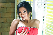 Busty Meena Yen strips red dress and plays with big dildo