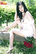Hana seated on wooden bench in dress breasts bared wearing high heels