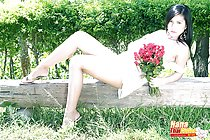 Reclining on bench holding bunch of flowers wearing high heels